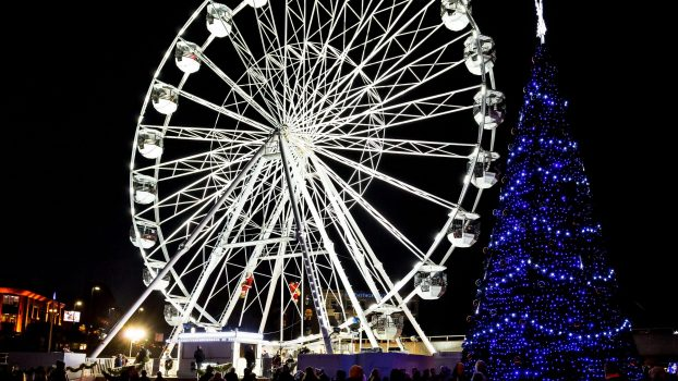 Huge outdoor  illuminated Christmas tree with ferris wheel in background in Bournemouth, Dorset, UK on 8 December 2018
