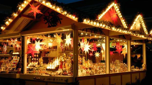 Illuminated Christmas fair kiosk with loads of shining decoration merchandise, no logos